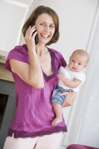 Mother in living room using telephone holding baby smiling